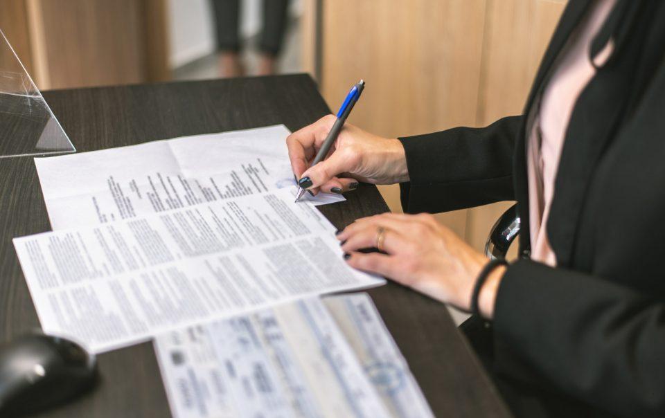 Verkäufer des Unternehmens und der Käufer sitzen gemeinsam beim Notar und unterzeichnen den Kaufvertrag