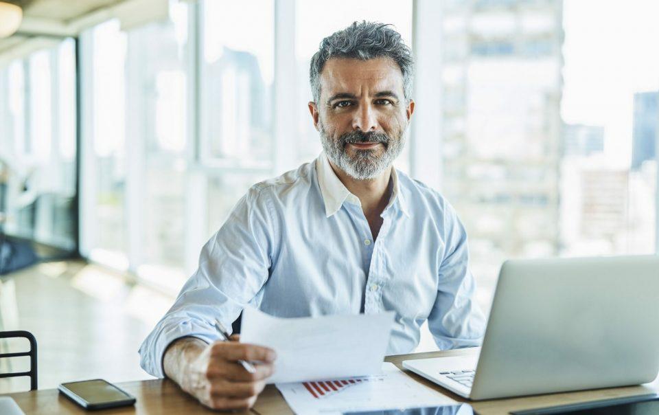 Mittelständischer Unternehmer sitzt am Schreibtisch und blickt in die Kamera