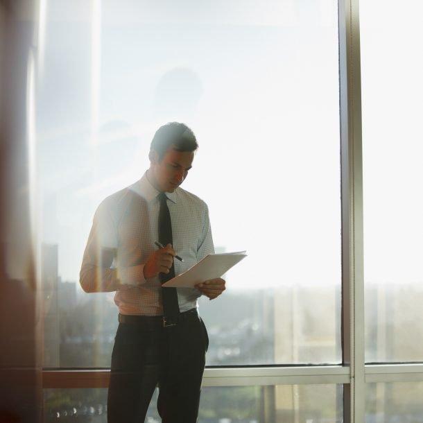 Berater liest im Flur den Letter of Intent bevor er es dem Senior Partner vorlegt