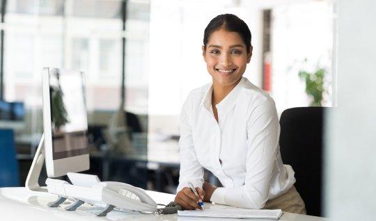 Junge Praktikantin sitzt am Schreibtisch und lächelt sympathisch in die Kamera