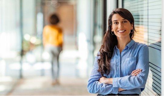 Junge M&A-Beraterin lehnt an der Glastür und lächelt sympathisch in die Kamera